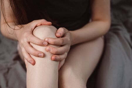 Cropped images of unrecognizable woman sitting on bed at home with knee pain, young woman massaging her painful knee, Health care concept. Selective focus Imagens