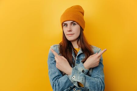 Questioned young female crossed arms over chest, gives two variants and advertises product, wears denim jacket, asks advice as cant pick something, pose over yellow studio background with copy space