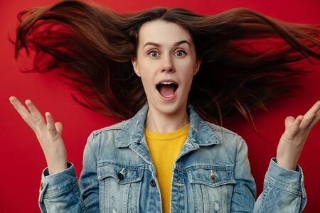 Portrait of young woman with flying hair in panic looks with surprised expression, feels nervous in stressful situation, wears denim jacket, opens mouth with stupefaction, isolated on red background