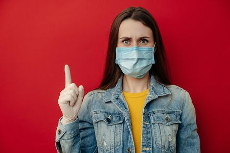 Young serious woman model wears protective medical mask, points away, demonstrates something at blank copy space for your advertisment or promotional text, looks at camera, isolated over on red wall. Imagens