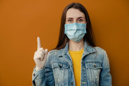 Studio shot of brunette woman wears protective medical mask, points away, demonstrates something at blank copy space for your advertisment or promotional text, isolated over on brown background Imagens
