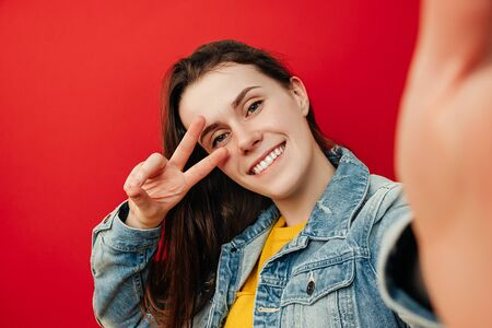Pleasant looking happy young woman with broad shining smile, doing selfie shot on mobile phone showing victory sign, dressed in denim jacket, poses against red background. People and lifestyle Imagens