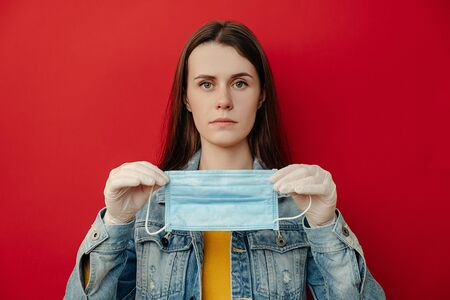 Portrait of young woman holding protective medical mask looks at camera, wears denim jacket and gloves, isolated over on red background. Epidemic illness, coronavirus 2019-ncov concept Imagens