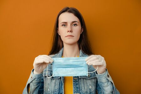 Young woman holding protective medical mask looks at camera, wears denim jacket and gloves, isolated over on brown background with copy space. Epidemic illness, coronavirus 2019-ncov concept Imagens