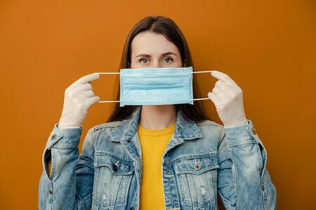 Portrait of woman protects face with mask, thinks abot risk of epidemic disease, has virus infection, looks at camera, isolated over on brown background. Concept safety, coronavirus, virus protection