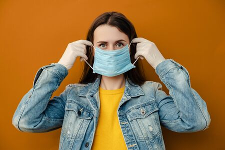 Woman wears protective medical mask not to infect other people, has virus infection, wears denim jacket, poses indoor against brown wall. Epidemic pandemic spreading coronavirus 2019-ncov concept