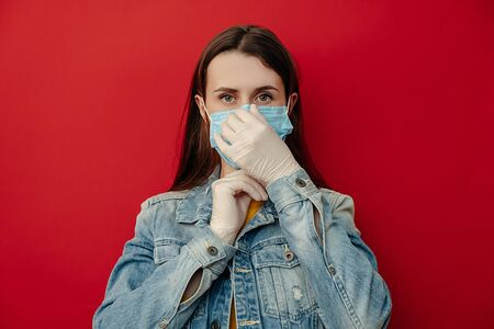 Horizontal shot of woman putting protective medical mask, looking confident at camera, wears denim jacket and gloves, isolated against red background. Epidemic illness, coronavirus 2019-ncov concept