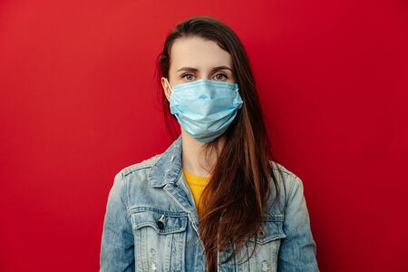 Serious young woman wears respirator mask, looking confident at camera, wears denim jacket, isolated against red background. Epidemic pandemic spreading coronavirus 2019-ncov concept