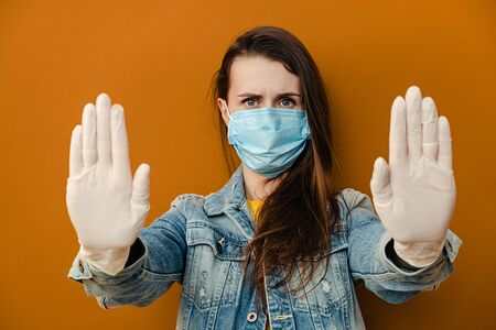 Portrait of serious woman in sterile face mask gloves, pulls hands towards camera in stop gesture, wears denim jacket, isolated over on brown background. Quarantine pandemic coronavirus virus concept