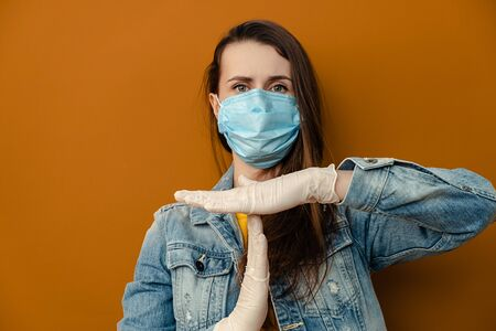 Portrait of dissatisfied woman in medical sterile face mask gloves, shows timeout gesture, needs stop, isolated over on brown wall. Epidemic pandemic spreading coronavirus 2019-ncov, flu virus concept