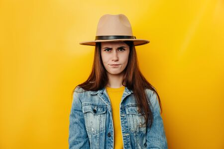 Serious unhappy woman in hat frowns from displeasure, raises eyebrows, dissatisfied with something, wears denim jacket, isolated over yellow background. Negative human emotions and feelings concept Banco de Imagens