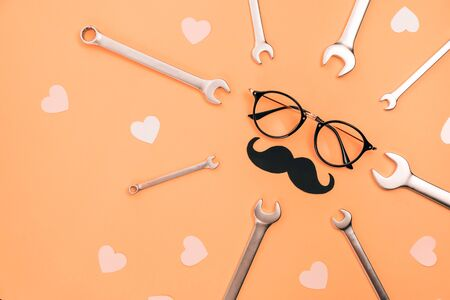Holiday concept made with eyeglasses, stylish black paper photo booth props moustaches, many little hearts and combination wrenches on orange background. Copy space for inscriptions. Creative idea.