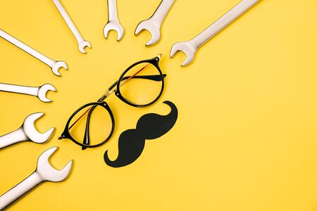 Creative holiday concept made with transparent glasses, stylish black paper photo booth props moustaches and combination wrenches on yellow background. Copy space for inscriptions. Imagens