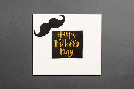 Card with phrase happy father's day and retro stylish black paper photo booth props moustaches on grey background. Minimal style and holiday concept. Flat lay, copy space Imagens