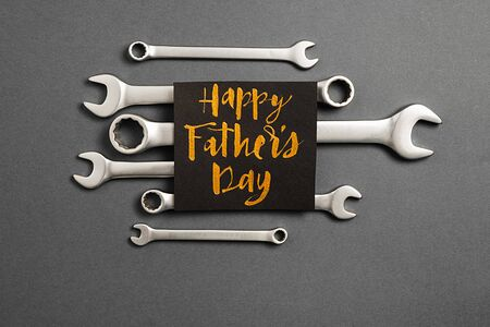 Combination wrenches, card with phrase happy father's day on grey background. Minimal style and holiday concept. Flat lay, copy space