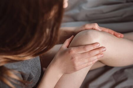Side view of tired young woman siting bed at home or hotel room massaging knee, feeling pain. Girl suffering from ache in leg, feeling unwell, health problem concept, osteoarthritis. Selective focus Imagens