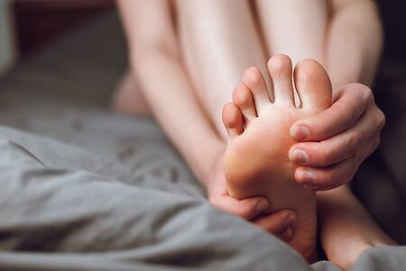 Tired female feeling discomfort rubbing her sore and painful foot and toes, during exercise sitting on bed at home. Woman foot massage to relieve pain from ache. Tense sore sprained muscle Imagens