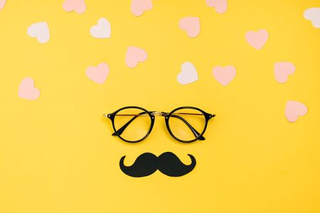 Creative holiday concept made with transparent glasses, stylish black paper photo booth props moustaches and many little hearts on yellow background. Copy space for inscriptions.