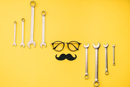Creative flat lay composition with transparent glasses, stylish black paper photo booth props moustaches and combination wrenches on yellow background copy space. Fathers day masculinity concept blog