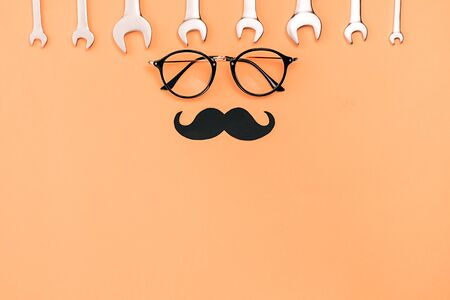 Creative holiday concept made with transparent glasses, stylish black paper photo booth props moustaches and combination wrenches on orange background. Copy space for inscriptions.