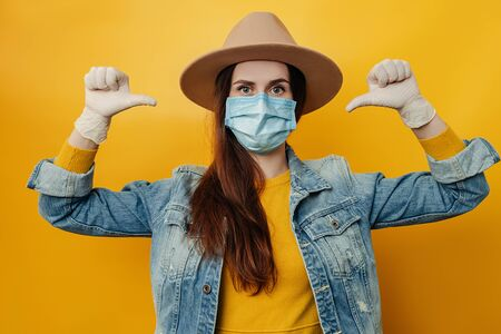Brunette woman in hat wears protective medical mask not to infect other people, pointing thumbs on herself, looks at camera, isolated over on yellow background. Concept coronavirus, virus protection Imagens