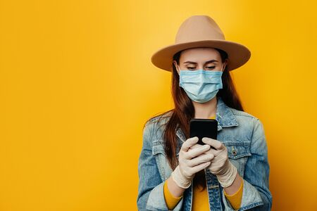 Horizontal shot of woman in medical sterile face mask gloves, chats online with friends, checks notification received on email, being always in touch, wears denim jacket. Pandemic coronavirus concept