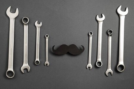 Creative flat lay overhead top view retro stylish black funny paper moustache and combination wrenches on grey background with copy space. Men health awareness month fathers day masculinity concept