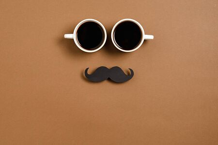 Creative flat lay composition with two cup coffee and retro stylish black paper photo booth props moustaches on brown background, space for text. Happy Father's Day Imagens