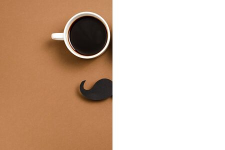 Close up of hot cup coffee, stylish black paper photo booth props moustaches on brown and white background. Copy space for inscriptions. Creative idea, minimal composition Imagens