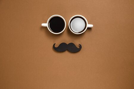 Two cup coffee and retro stylish black paper photo booth props moustaches on brown background. Minimal style and holiday concept. Flat lay, copy space