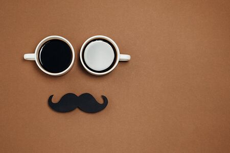 Men health awareness month fathers day masculinity concept. Flat lay composition with two cup coffee and retro stylish black paper photo booth props moustaches on brown background, space for text.