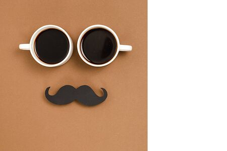 Two cup coffee, stylish black paper photo booth props moustaches on brown and white background. Copy space for inscriptions. Holiday Concept.