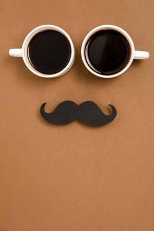 Vertical images of two cup coffee and retro stylish black paper photo booth props moustaches on brown background, space for text. Men health awareness month fathers day masculinity concept.