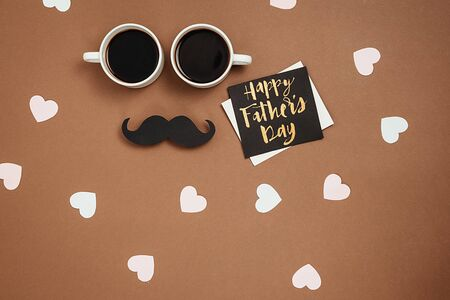 Two cup coffee, stylish black paper photo booth props moustaches, card with phrase happy father's day and many little hearts on brown background. Copy space for inscriptions. Holiday Concept.