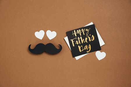Creative flat lay composition with little hearts, card with phrase happy father's day and retro stylish black paper photo booth props moustaches on brown background. Space for text