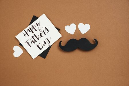 Horizontsl images of many small hearts, card with phrase happy father's day and retro stylish black paper photo booth props moustaches on brown background. Holiday concept. Imagens