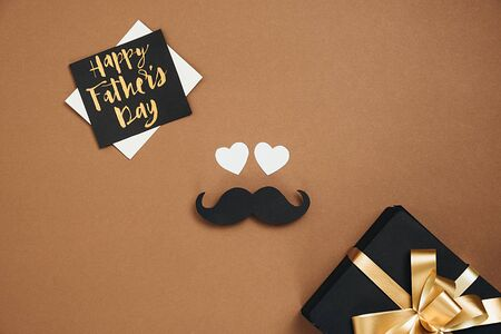 Happy fathers day concept. Top view of handmade gift box, card with phrase happy father's day and retro stylish black paper photo booth props moustaches on brown background. Flat lay, copy space