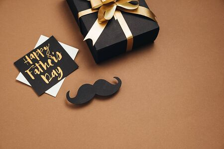 Horizontsl images of handmade gift box, card with phrase happy father's day and retro stylish black paper photo booth props moustaches on brown background. Holiday concept.