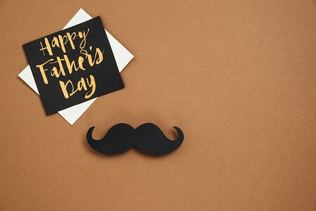 Flat lay overhead top view card with text Happy Father's Day and retro stylish black paper photo booth props moustaches on brown background. Space for text. Minimal composition