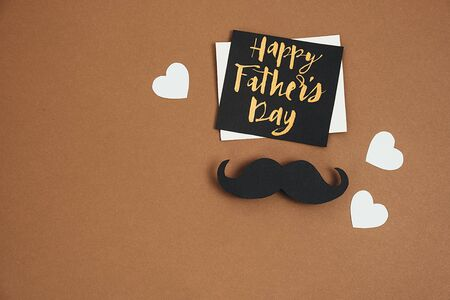 Close up of stylish black paper photo booth props moustaches, many little hearts and card with phrase happy father's day on brown background. Copy space for inscriptions. Creative idea.