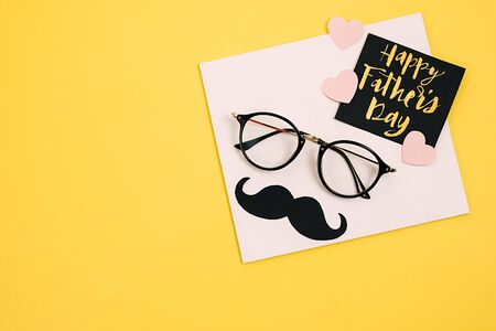 Creative flat lay composition with card text Happy Father's Day, transparent glasses, moustache photo booth props and little pink hearts on yellow background copy space. Concept blog social media