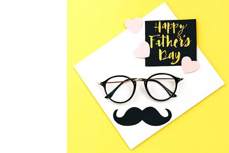Close up of eyeglasses, stylish black paper photo booth props moustaches, many little hearts and card with phrase happy father's day on yellow background. Copy space for inscriptions. Creative idea.