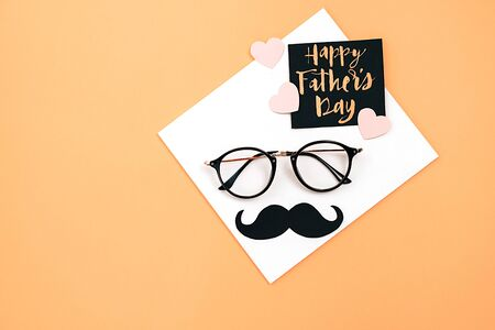 Happy fathers day concept. Top view of eyeglasses, card with phrase happy father's day and retro stylish black paper photo booth props moustaches on orange background. Flat lay, copy space Imagens