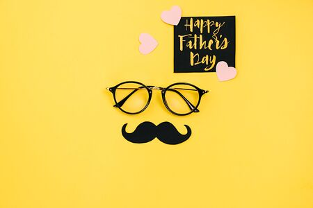 Happy fathers day concept. Top view of eyeglasses, card with phrase happy father's day and retro stylish black paper photo booth props moustaches on yellow background. Flat lay, copy space