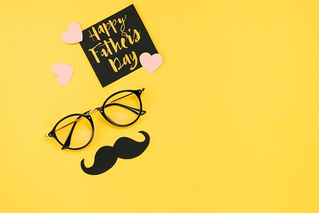Close up of eyeglasses, stylish black paper photo booth props moustaches, many small hearts and card with phrase happy father's day on yellow background. Copy space for inscriptions. Creative idea.