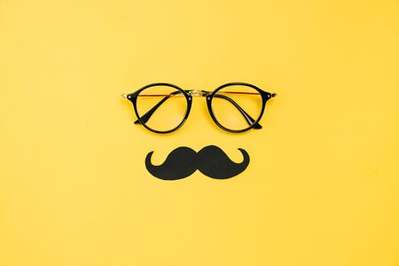 Creative flat lay overhead top view transparent eyeglasses and retro stylish black paper photo booth props moustaches on yellow background with copy space. Fathers day concept Imagens