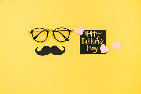 Top view of eyeglasses, card with phrase happy father's day, many little hearts and retro stylish black paper photo booth props moustaches on yellow background. Flat lay, copy space