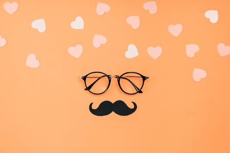 Eyeglasses, stylish black paper photo booth props moustaches and many little hearts on orange background. Copy space for inscriptions. Father's Day Holiday Concept. Imagens
