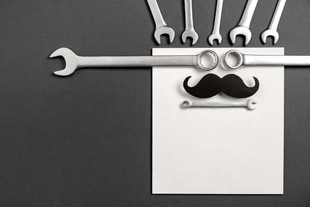 Creative holiday concept made with stylish black paper photo booth props mustaches, combination wrenches on gray and white background. Copy space for inscriptions.