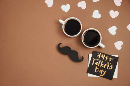 Flat lay composition with little hearts, two cup coffee, card with phrase happy father's day, retro stylish black paper photo booth props mustaches on brown background. Creative minimal composition